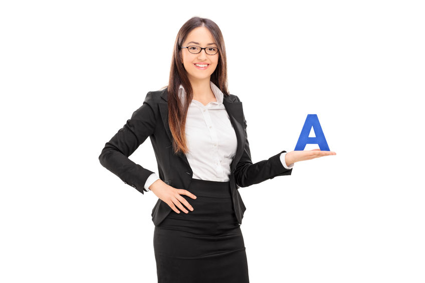 41849844 - young female school teacher in a black suit holding the letter a and looking at the camera isolated on white background